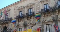 La facciata del Municipio con le mongolfiere e le maschere in cartapesta allestite dai ragazzi del carcere minorile