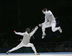 U.S. fencer Jonathan Tiomkin soars above Russian opponent Renal Ganeev in the bronze-medal bout of the men's team foil competition at the Athens Olympic Games. Russia went on to win, 45-38.