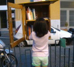 Una bambina mette dei libri nella libretta di piazza Garibaldi