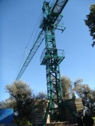 L'enorme gru installata per sollevare e depositare nel cantiere i veri pezzi della struttura man mano che vengono smontati